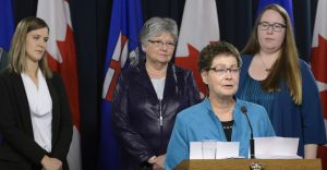 Woman in glasses and brown hair stands at podium while three women stand behind her