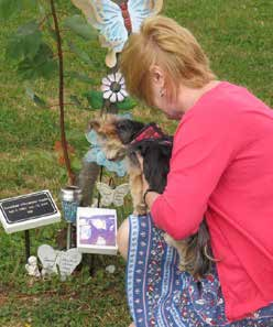 Woman and dog crouch in front of a memorial display in a park