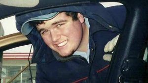 man in blue jacket smiles through car door