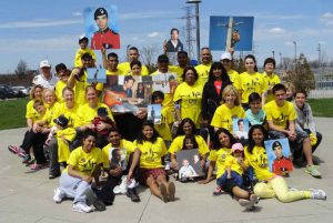 Group of people in yellow T-shirts holding several photos of a young man