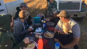 family sits at dinner table in field with equipment