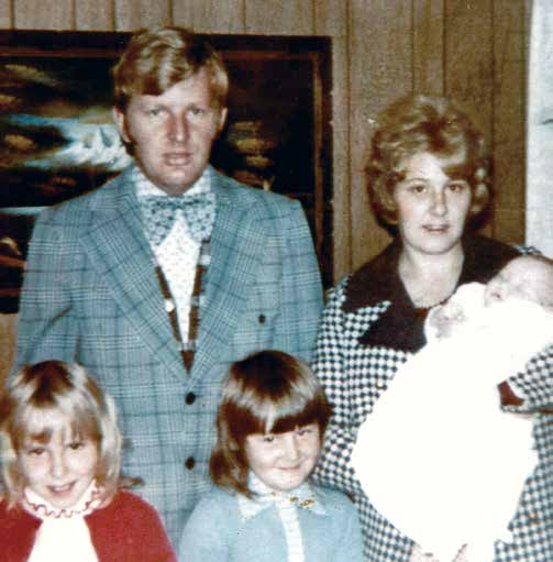 Man in suit and bowtie stands with woman and three young girls