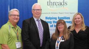 Two men and two women stand in front of Threads of Life banner sign