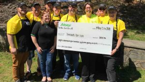 Group of people wearing Sobeys hats stand with presentation cheque