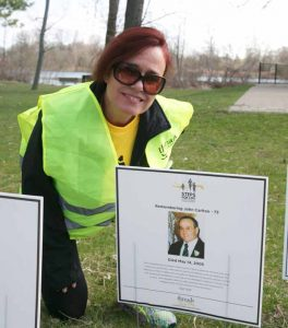 Woman with red hair crouched in front of a sign with man's face