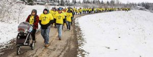Walkers in yellow T-shirts walk along path surrounded by snow