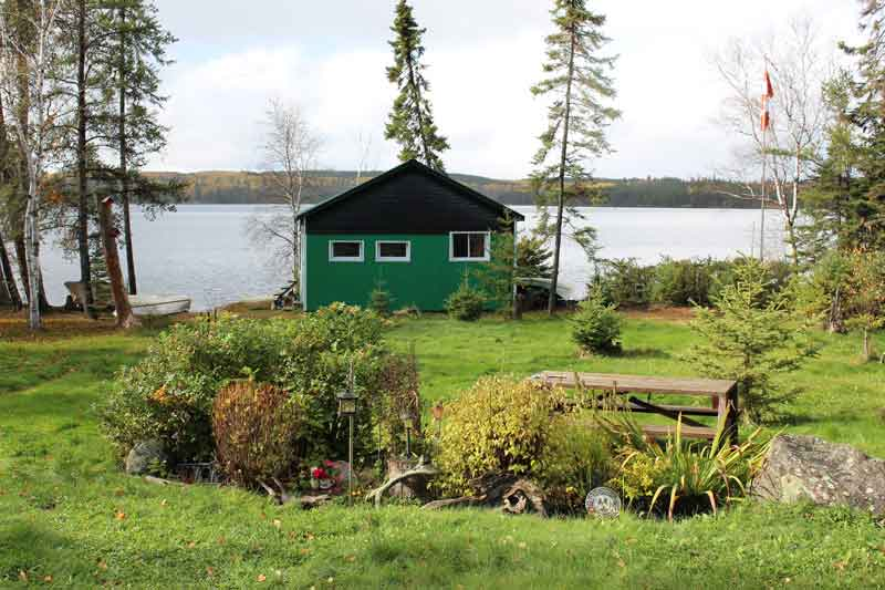 small green and black cottage on shore of lake with beautiful garden in front