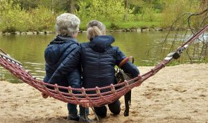 rear view of two older women with grey hair sitting in a hammock beside a body of water
