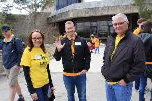 Woman in yellow t-shirt stands with two men, all are smiling