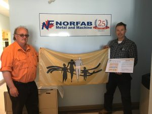 """Two men stand holding Steps for Life flag in front of Norfab Metal and Machine sign. One man holds plaque that says """"Proud Supporter"""""""