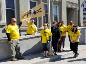 Group of people in yellow T-shirts stand with Steps for Life flag in front of Timmins City Hall