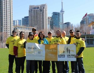 One Modern Toronto Team in yellow T-shirts stands with Toronto skyline behind them
