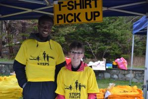 """Man and woman in yellow T-shirts stand in front of sign that reads """"T-Shirt Pick Up"""""""