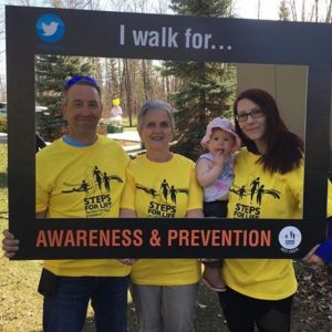 """Family in yellow t-shirts stands within a Twitter frame that reads """"I walk for... Awareness and Prevention"""". [Steps for Life Red Deer logo]"""