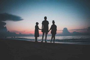 backlit silhouettes of three kids on a beach at sunset