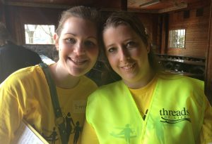 Two women wearing yellow T-shirt and vest smile for the camera. One is holding a clipboard.