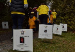 Adults and children in yellow T-shirts walking away down a path in front of signs bearing names and photos of workers.