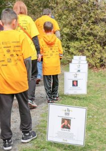 Families walking along path beside signs bearing faces and names. Back of T-shirts displays many sponsor logos.