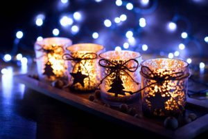 4 lit holiday votive candles in blue light
