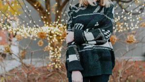 Woman in green sweater stands in front of lit holiday tree