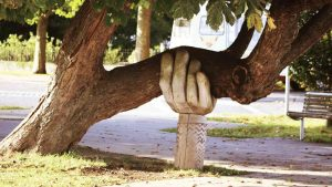a carved hand supports a leaning tree