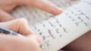 person holding pen is writing a letter. Focus is blurred and writing is illegible.