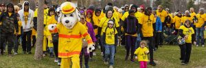 Group of walkers in yellow T-shirts with a white dog maskot in a yellow suit