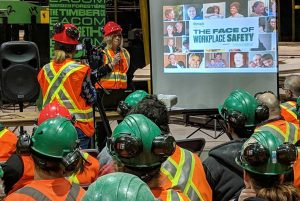 People in green hard hats and safety vests.