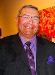 Smiling man in suit and bright purple shirt and tie