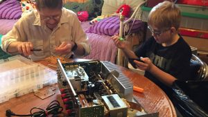 Man and young boy working on project at table.