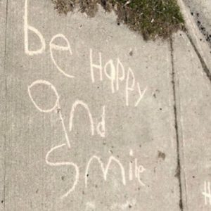 """chalk message on sidewalk reads """"be happy and smile"""""""