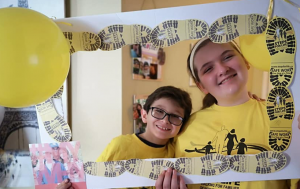 girl and boy smiling inside of frame lined with yellow boot prints