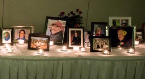 Table with photos of people and candle glowing in front of each one.