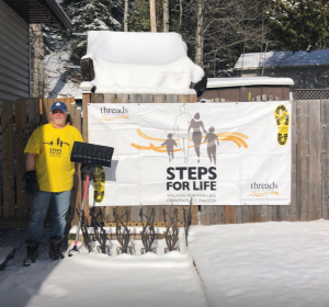 man stands with shovel in front of Steps for Life sign