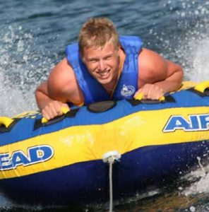 teenage boy holds on tightly to tube being pulled over the water