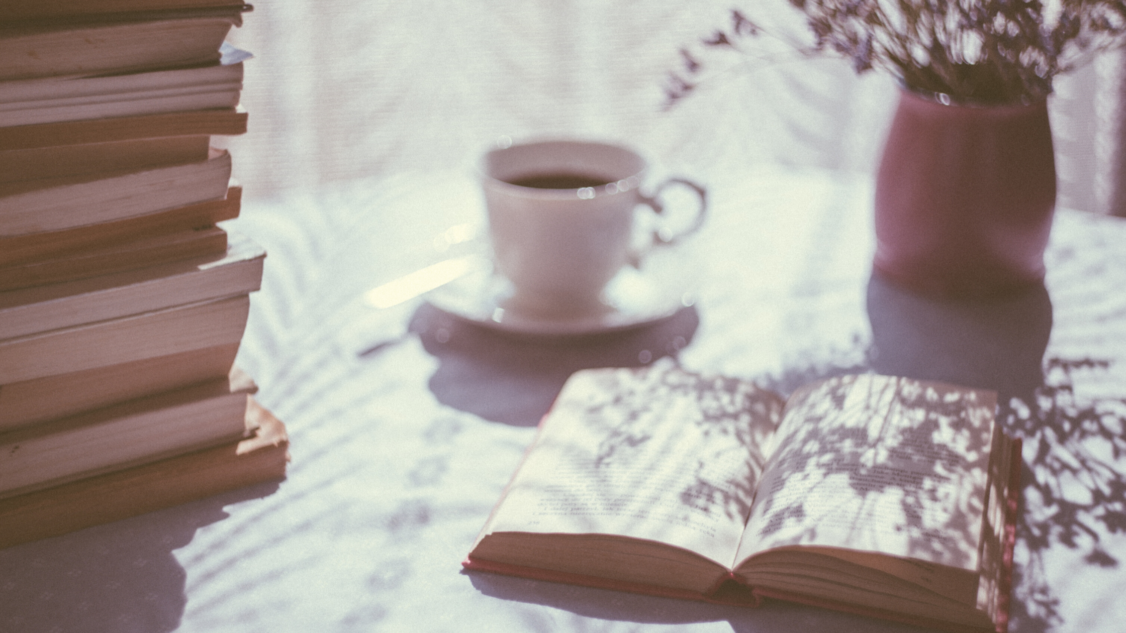 Filtered sunlight cast over a table with an open book, a stack of books, a plant, and a cup and saucer holding dark liquid
