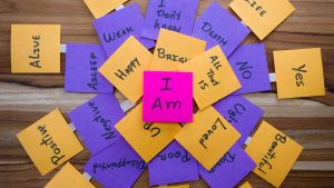 """Post-It notes arranged in a circle, each with a short message printed on it, such as happy, all that is, loved, etc. In the centre, there is a pink post it note that reads """"I am"""""""