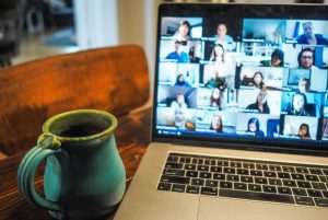 A blue coffee mug rests beside an open laptop displaying a grid of faces talking on a video conference