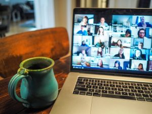 blue mug of coffee rests on table beside an open laptop with a grid of faces on a videoconference