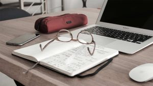 reading glasses lying on an open notebook in front of an open laptop