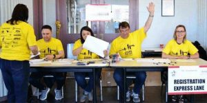 smiling volunteers seated at a table. One has his arm raised.