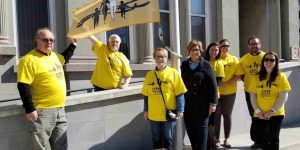 group of men and women in yellow t-shirts stand with an orange Steps for Life flag