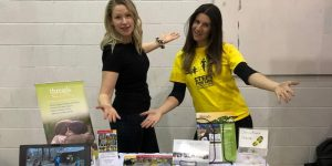 two women standing behind tradeshow table with arms wide