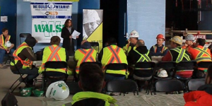 woman standing in front of group of men in safety vests