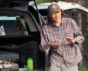 young man in cap and plaid shirt stands beside the rear of a vehicle. His hands are raised as though he is mid-sentence