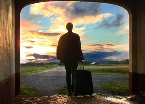 silhouette of person standing in doorway with a suitcase