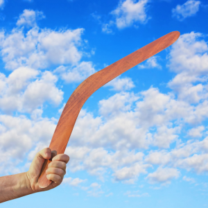 hand holding orange boomerang against a blue sky with fluffy clouds