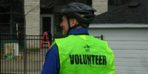 Man on bicycle with Steps for Life volunteer vest