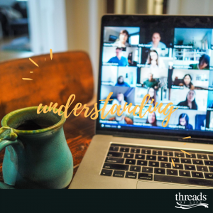 blue mug filled with coffee rests beside an open laptop with a video conference call visible on screen.