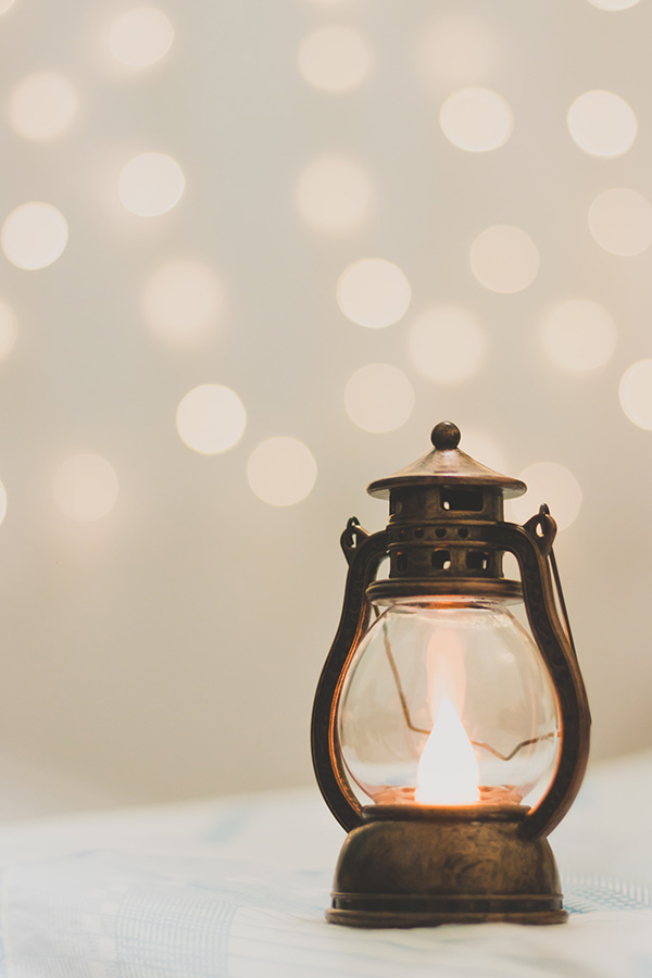 a lit lantern rests on a white surface with dots of light speckled on the wall behind